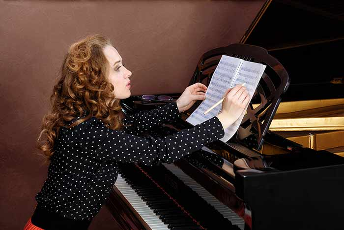 Woman on the piano writing feat