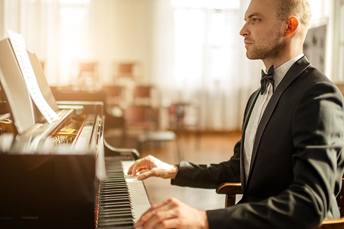 man performing on the grand piano feat