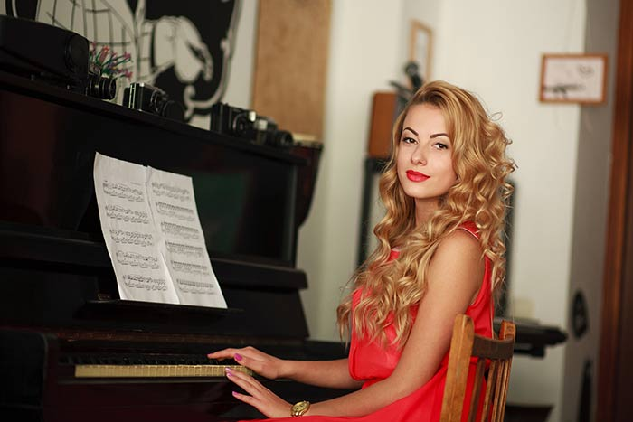 woman in red sitting in front of the piano feat