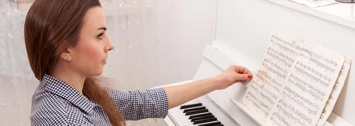 woman reading piano music sheet